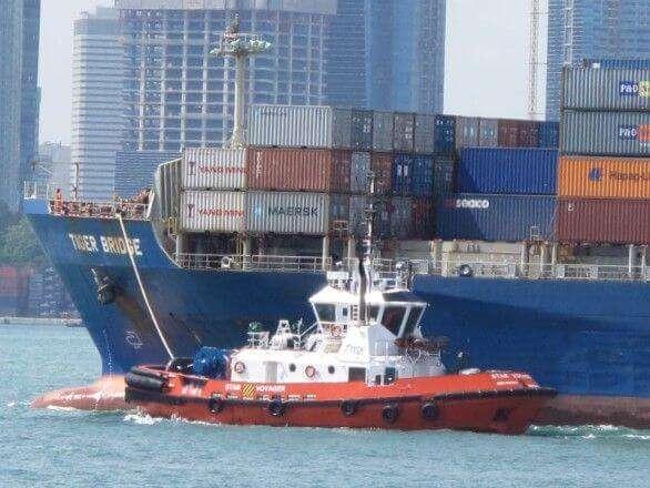 Containerschiff mit Schlepper